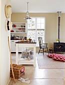 Kücheninsel in offener Küche und Bodenkissen vor Kaminofen in ländlichem Wohnraum
