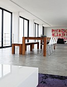 Modern dining area with bench and Eames shell chairs on polished concrete floor in Johannesburg art collector's loft apartment