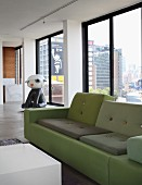 Polder sofa in shades of green and contemporary sculpture in background in front of continuous glass wall of loft apartment