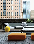 Designer lounger and ottomans on loft terrace; view of cityscape in Johannesburg, South Africa