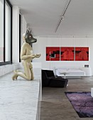 Sculpture of man with animal mask on marble counter with base cabinets and red triptych artwork in loft apartment