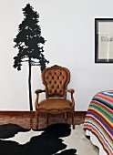Antique chair with brown leather cover in front of stencilled tree motif on wall, cowhide rug on mosaic wooden floor next to partially visible bed