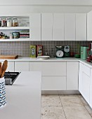 Corner of counter in fitted kitchen with white cabinet doors and sand-coloured stone floor