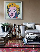 Stacked books and retro metal toy car on glass table; grey armchairs below portrait of Marilyn Monroe on grey brown wall