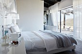 Double bed in modern bedroom with ensuite bathroom in background next to floor-to-ceiling terrace windows with fantastic view