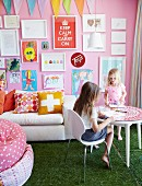 Children playing at round table, white sofa below collection of framed children's drawings on pink wall and green, lawn-effect carpet