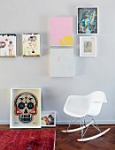White, Charles Eames rocking chair below various pictures on wall; framed modern picture of skull on floor
