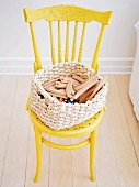 Wooden toys in basket on yellow-painted Thonet chair