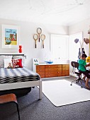 Child's bedroom - boy sitting on chair next to coat rack, bed, sideboard and tennis racquets hung on wall