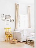 Basket on floor, yellow-painted chair and collection of silver trays on wall next to white sofa below window with floor-length curtains