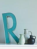 Deko-Buchstabe und handgefertigte Vasensammlung auf Ablage