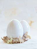 White eggs in nests of feathers with Easter bunnies