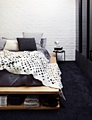 White blanket with pattern of holes on bed with integrated shoe rack on black carpet