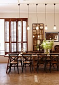 Long wooden table, bistro chairs and row of industrial-style pendant lamps; vintage decor with folding interior shutters and stone floor