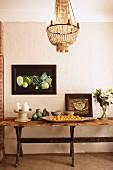 Rustikaler Holztisch dekoriert mit Keramik- und Porzellangeschirr, Blumenstrauß und Obstschale, Vintageflair mit gerahmten Gemälden und Kronleuchter