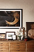 Various oil paintings, artistic crucifix and flowering orchid on wooden sideboard below painting on white-painted brick wall