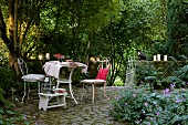 Atmospheric terrace seating area - white vintage metal chairs and table on cobbled floor in front of lit candles on low wall in densely planted garden