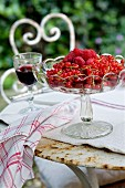 Glass dish of fresh redcurrants and raspberries on vintage metal table in garden