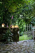 Terrace with lanterns on low, mossy wall with white metal gate leading to densely planted garden