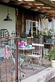Gartenstühle und Tisch aus Metall auf Veranda, Zäune aus altem Metallgitter vor rustikalem Häuschen mit Mauerwerk und teilweise Holzverkleidung