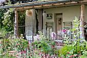Blühender Garten vor altem Haus, mit überdachter Veranda, verschiedene Vintagemöbel aus Metall