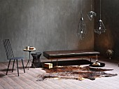 Brown leather bench, animal-skin rug and Industrial-style, metal pendant lamps in corner of room