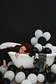 Woman lying exhausted in bathtub filled with balloons