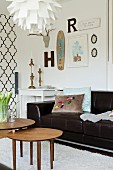 Set of 50s-style side table in front of black leather sofa, ogee-patterned wallpaper and vintage ornaments in background