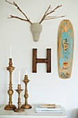Old skateboard, ornamental letter and stylised animal head with twig antlers on wall above turned candlesticks
