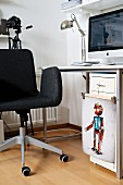 Dark grey swivel chair at desk with computer; clips holding colourful illustration of robot on filing cabinet