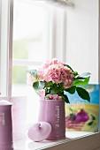 Pastellrosa Hortensie in hellviolettem Krug am Fenster