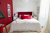 Framed pictures on red striped wall next to bed with red headboard