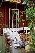 Hellgrau lackierte Holzbank mit Kissen und Korb, im Hintergrund schlichtes Holzhaus