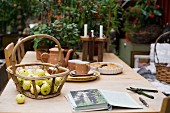 Basket of apples and rustic coffee service on wooden table