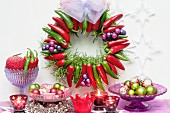 Festive arrangement with Advent wreath made of red and green chilli peppers, baubles, candles and stars