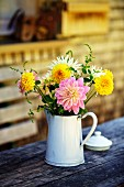 Dahlias in old, white enamel jug on outdoor table