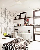 Black & white bedroom with bed and wall-mounted shelving above desk