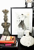 Vase with three-dimensional floral details, stacked books, antique metal candlestick and framed drawing of woman on cabinet