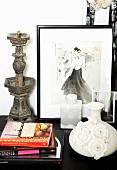 Vase mit Blumenapplikationen, Bücherstapel, antiker Metallkerzenständer und gerahmte Zeichnung einer Frau auf Kommode