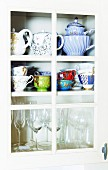 Teapots, cups and glasses in crockery cupboard with lattice door
