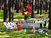 Mirror with red metal frame hanging on tree & white, wire mesh outdoor furniture with scatter cushions in woodland clearing