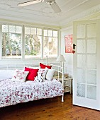 Country-style bedroom with white metal bed & floral bedspread in front of ribbon window