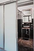 Blick durch offene matte Glasschiebetür in Designerbad mit Waschtisch in filigraner Metallausführung
