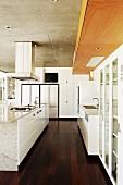 Modern, white kitchen with free-standing central island on dark wood floor