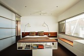 Half-height shelving in front of double bed flanked by bedside lamps in modern bedroom with glass sliding elements