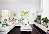Collection of scatter cushions on white leather corner sofa and ottoman in front of fireplace on dark wooden floor in modern living room