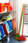 Brightly coloured, designer brooms and various home accessories on shop shelving