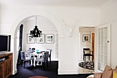 Living room with arched doorway leading to dining area with dining table & chairs