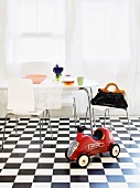 A red children's car with an eating area in the background on a black and white checked floor