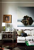 Vintage cabinet next to sofa with pale upholstery on antique wooden frame below landscape painting and gilt-framed portrait of woman